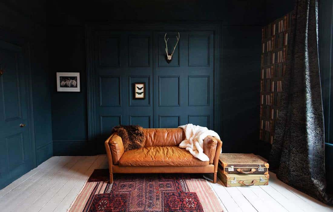 Living room with brown leather sofa, dark blue wall, hardwood floor and bookshelf