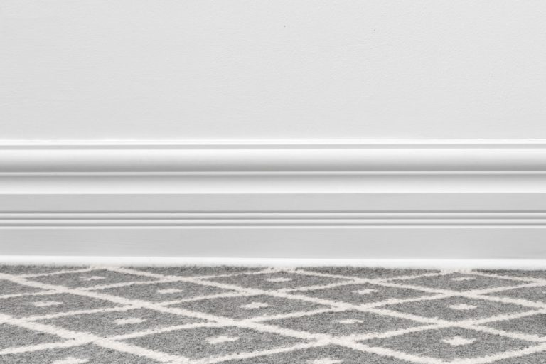 Living room with gray patterned carpet flooring, white baseboard, and a white painted wall, Should Carpet Go Under Baseboard?
