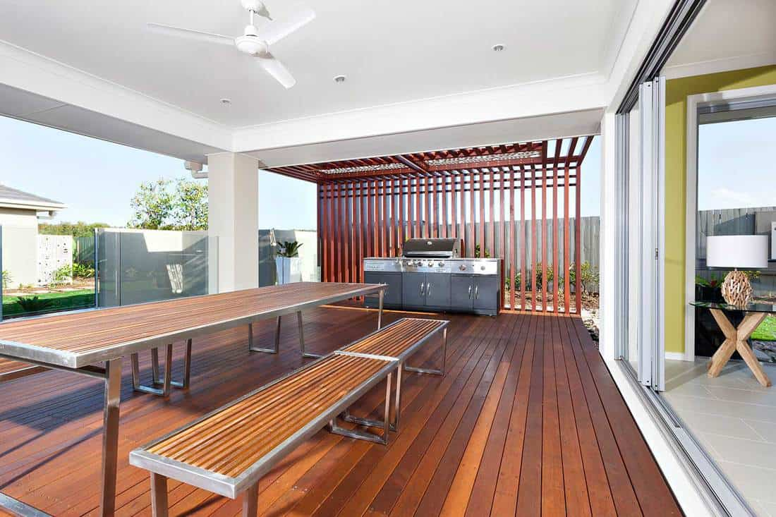 Long wooden table and benches with modern grill cabinet