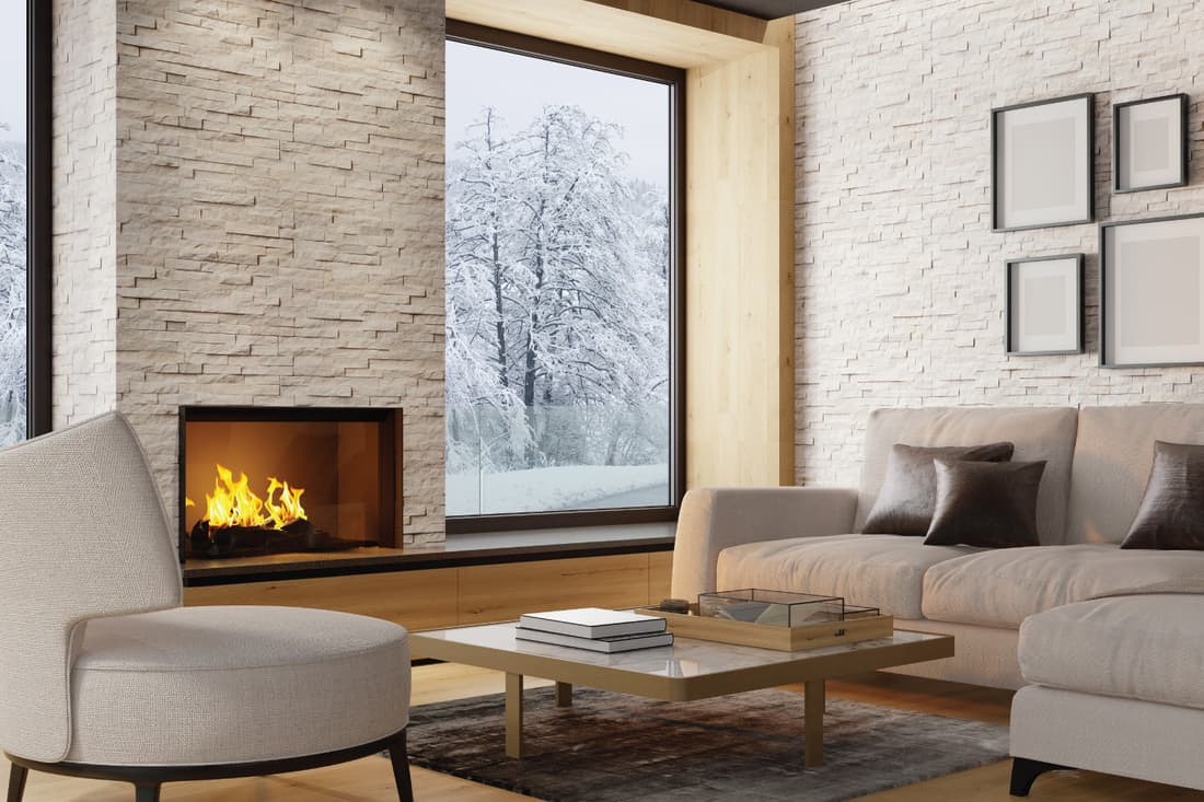 Luxurious Scandinavian light living room in country villa with natural stone slate wall, sofa and fireplace. Winter scene. off white with an flooring