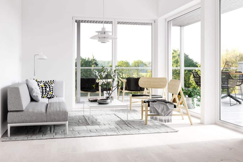 Luxurious contemporary living room with huge windows, gray sofa, and two wooden chairs, Can You Place An Area Rug Under The Coffee Table Only?