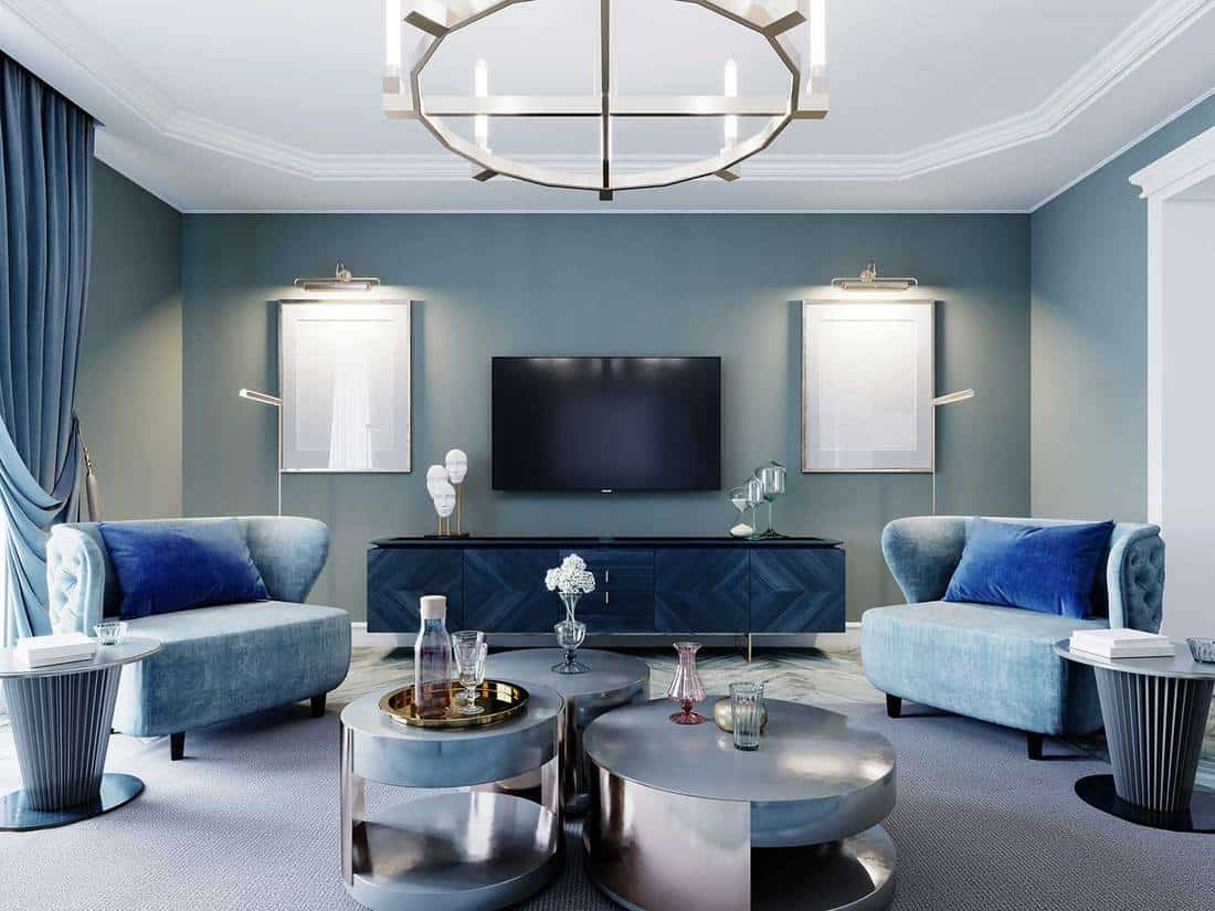 Luxurious fashionable living room with upholstered blue furniture, armchair, sofa and coffee table