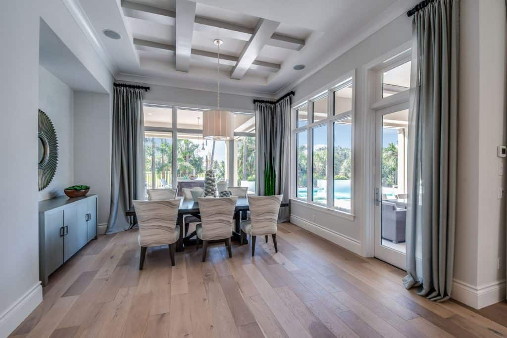 Luxurious interior of an ultra modern contemporary living room, wooden laminated flooring, gray ceiling high curtains, and picture windows