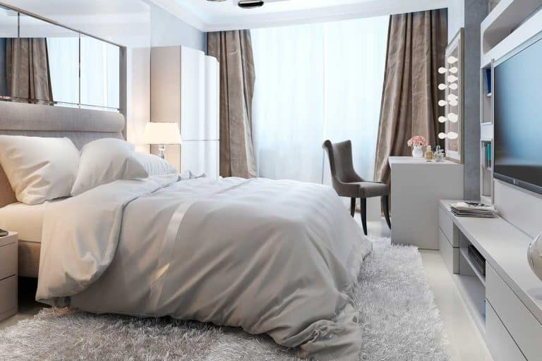 Luxury bedroom interior with cozy bed, vanity, TV and carpet rug on floor, Where To Place A Chair In A Bedroom [6 Amazing Options]