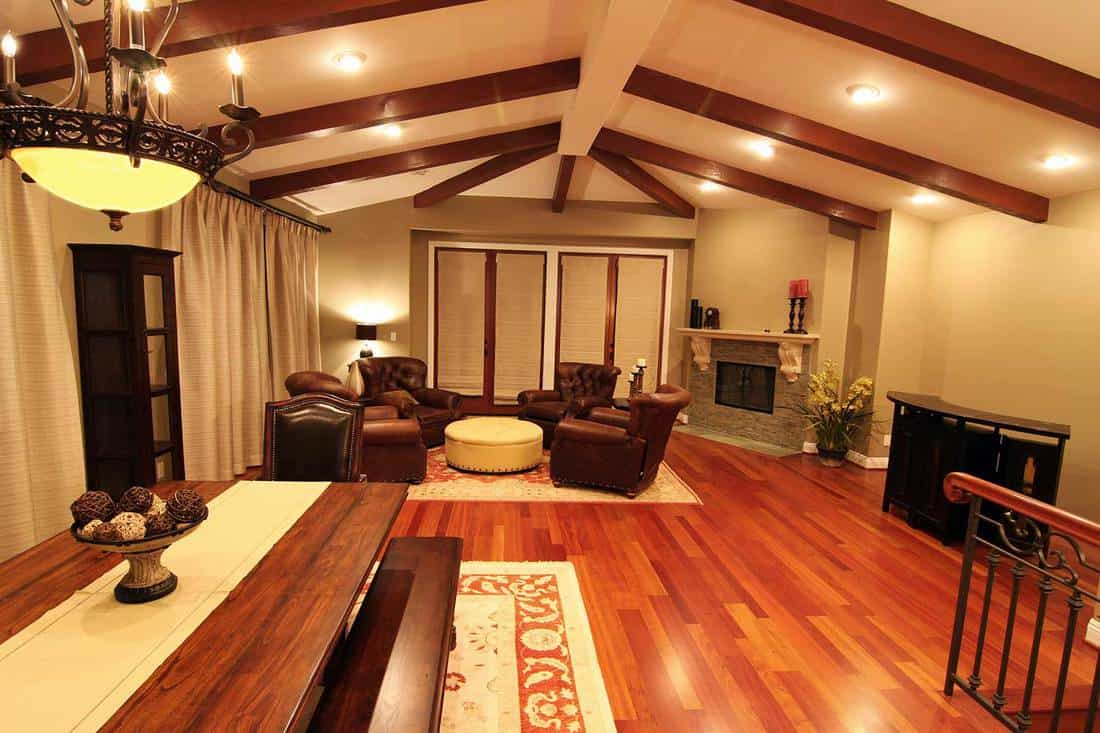 Luxury living room with fireplace, brown leather chairs and parquet floor