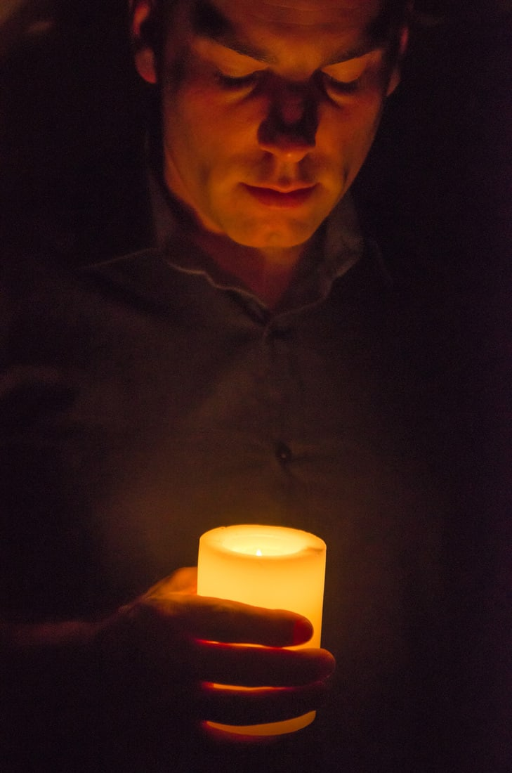 Masculine scented candle, Hand holding a lit candle in darkness