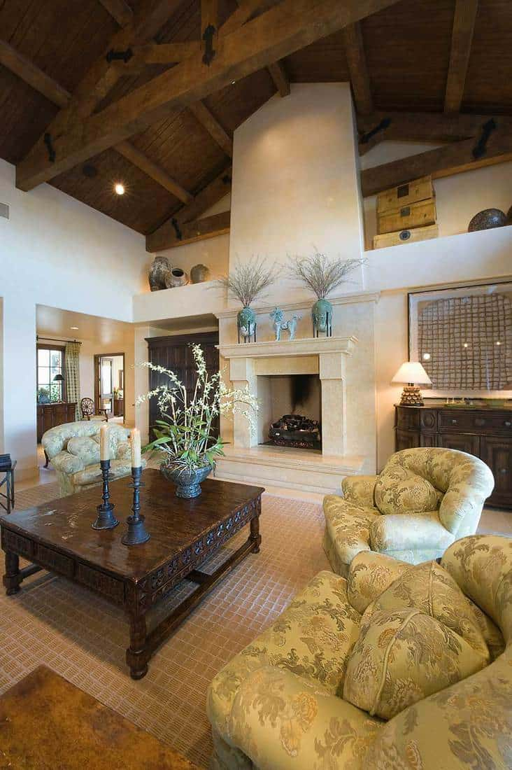 Matching armchairs and fireplace in living room with high wooden ceiling