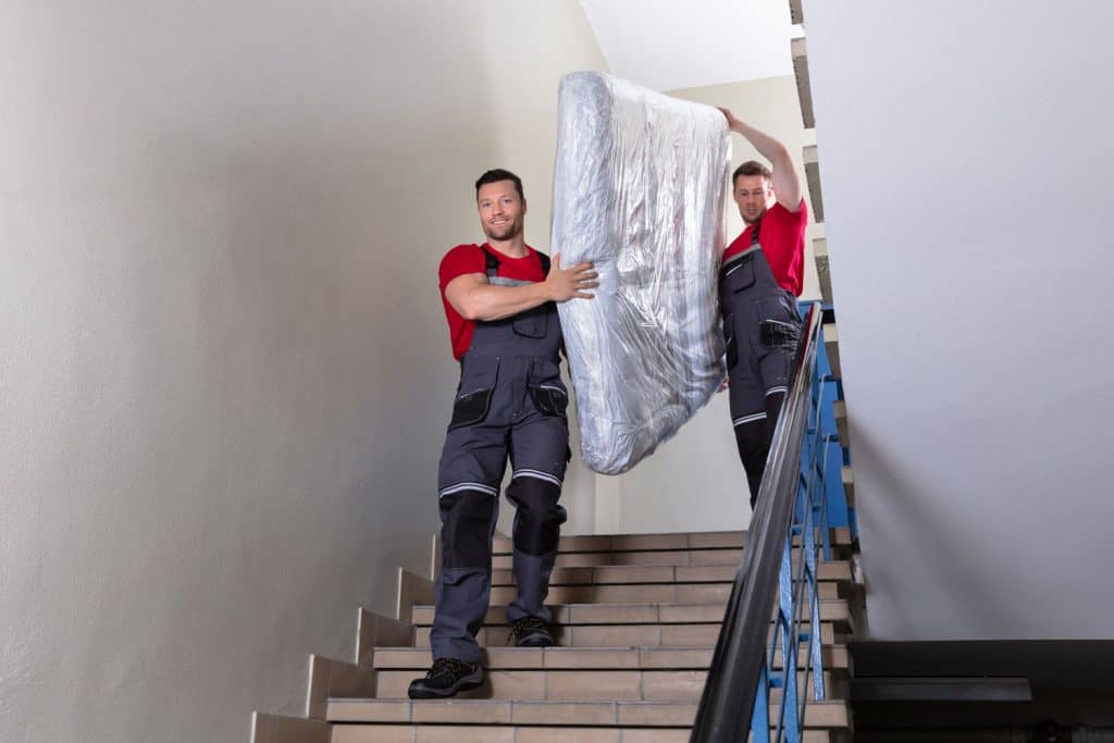 Mattress movers carrying a mattress along the stairs
