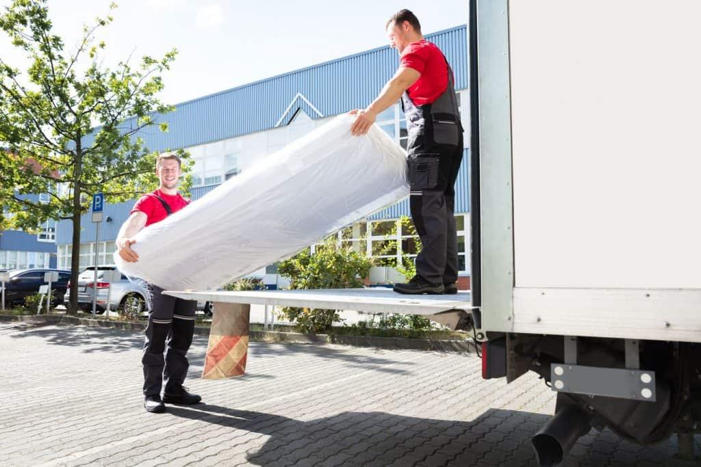 Mattress movers unloading a mattress of their cargo truck