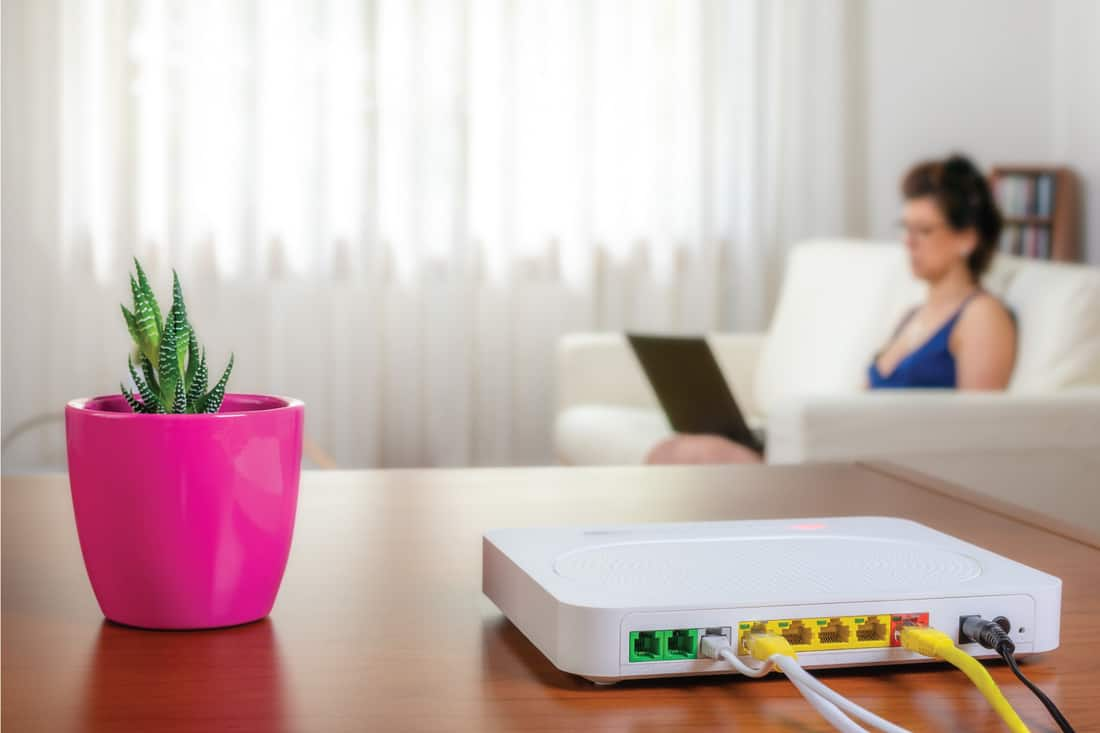 Modem router on a table in a living room. A woman using a laptop while sitting on the sofa