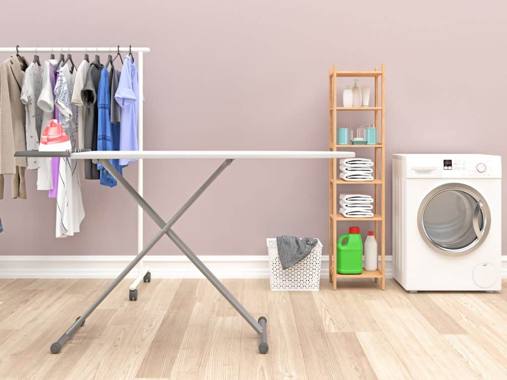 Modern Laundry Room With Washing Machine and cleaning supplies with a beautifully blush wall paint