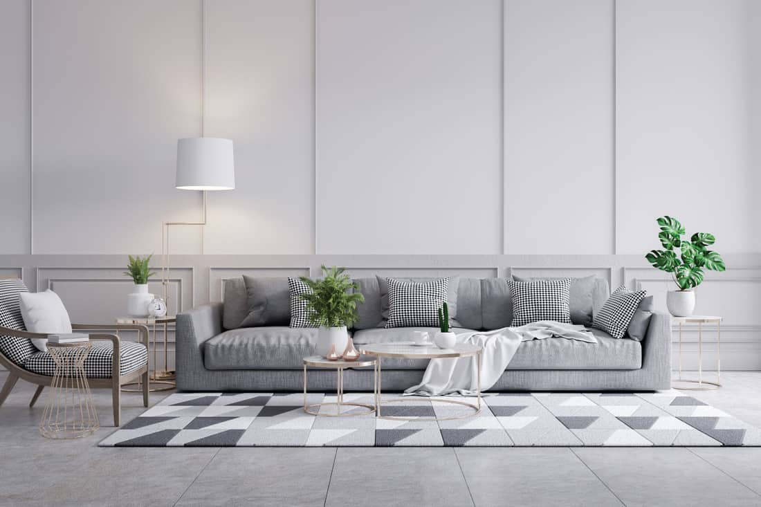 Modern classic interior of living room, gray sofa and marble table on white wall panels and concrete wall. white with geometric patterns