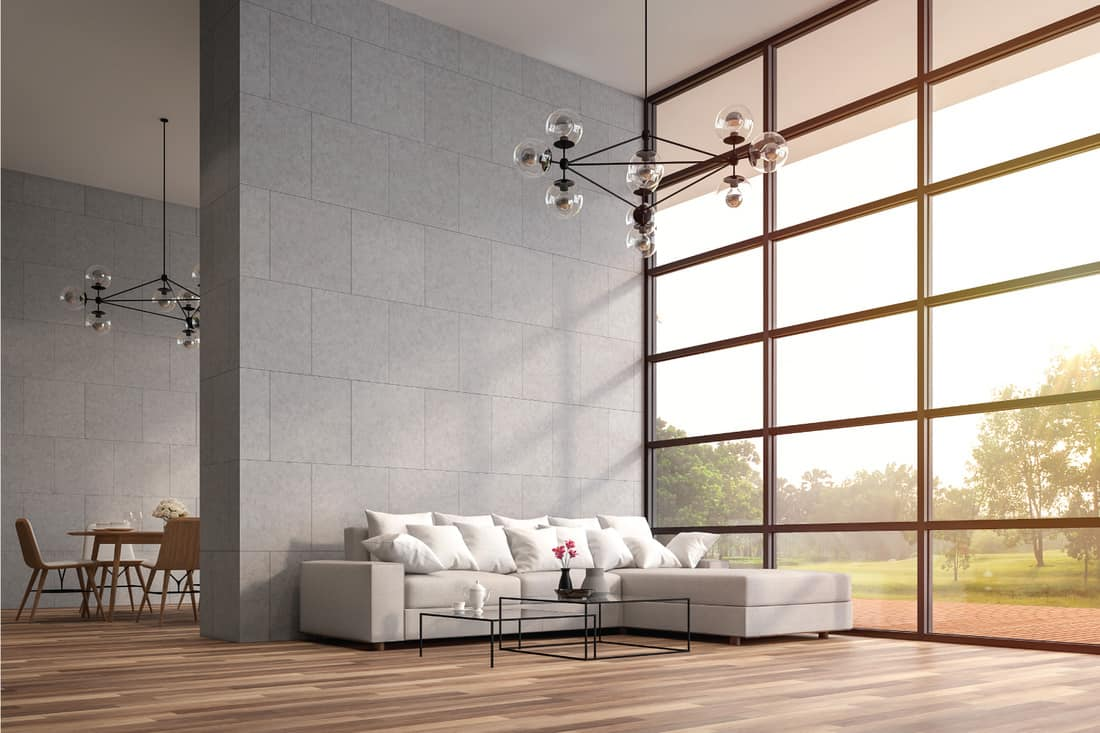 Modern high ceiling loft living and dining room. The Rooms have wooden floors ,decorate with white furniture,