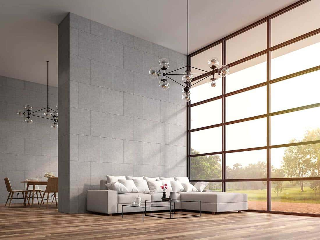 Modern high ceiling loft living room with wooden floors, white furniture, large window that overlooks wooden terrace and large garden
