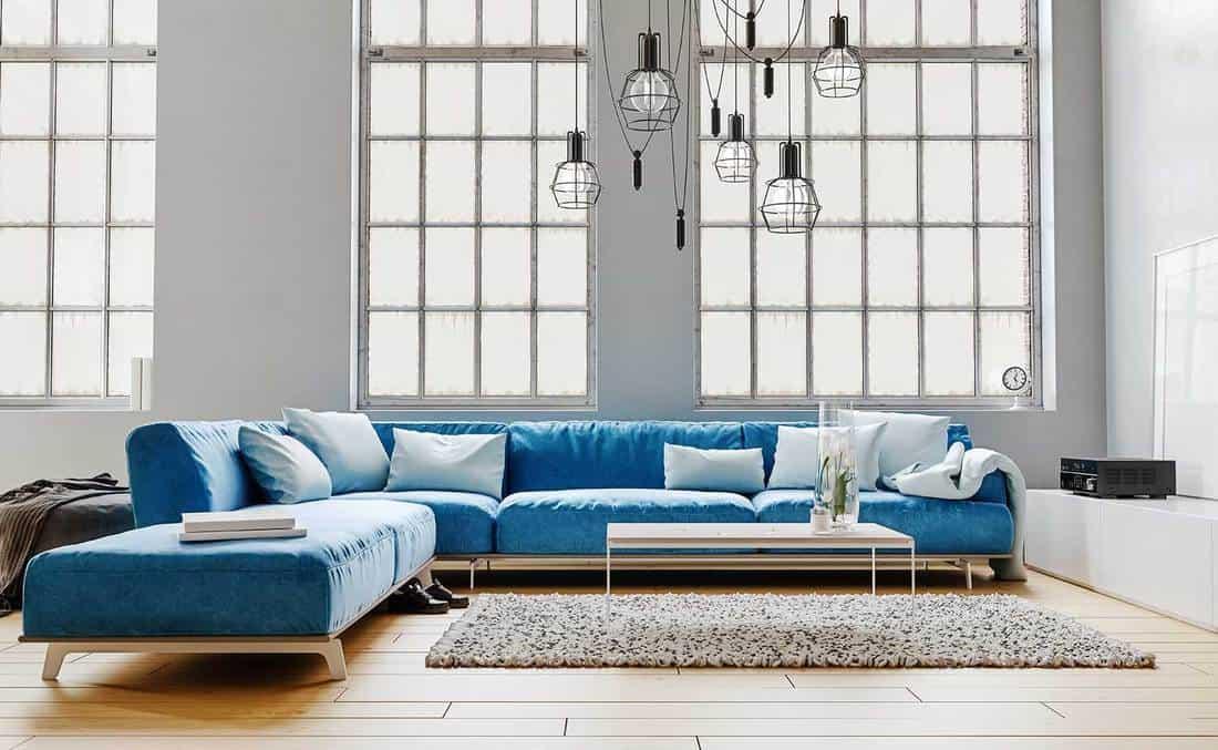 Modern interior design of living room with large modular blue velvet sofa, white pillows, high ceiling and huge windows