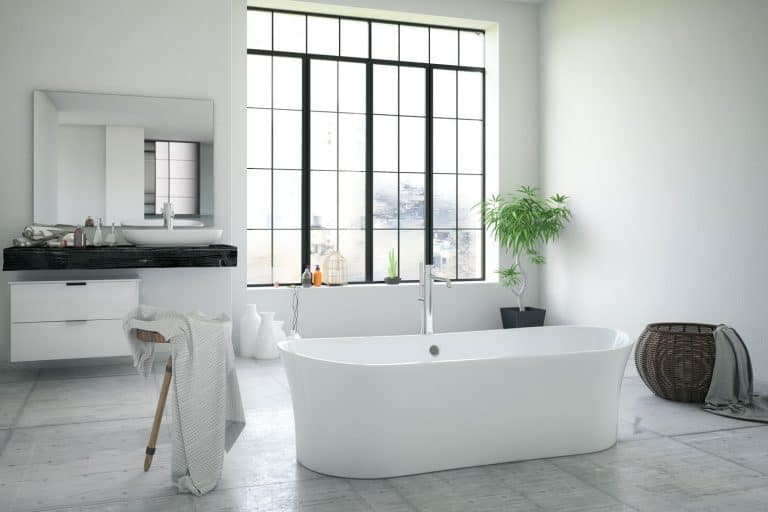 Modern interior of a bathroom with white painted walls, huge white bathtub, and a minimalist themed bathroom vanity, How Big Is A Bathtub? [A Breakdown Of Standard Dimensions]