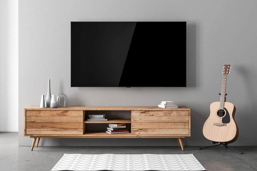 Modern interior of living room with a wall mounted TV and a wooden TV stand
