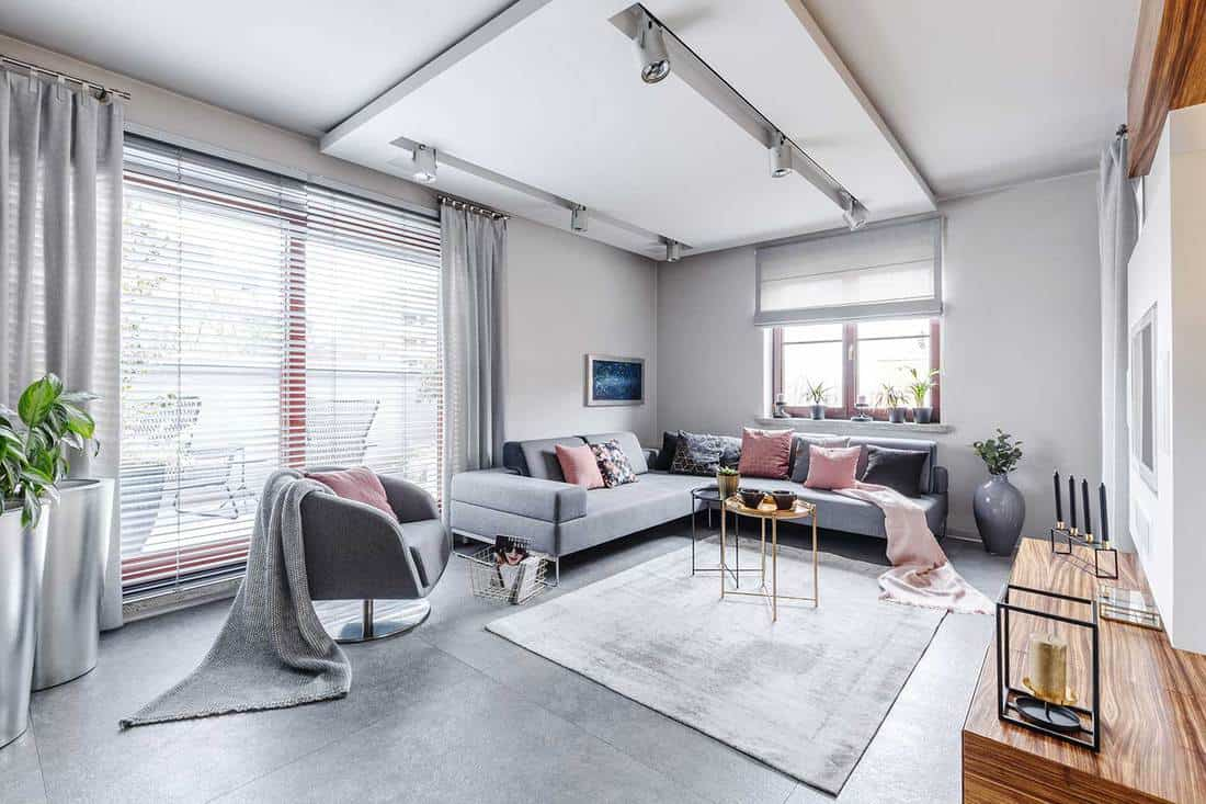 Modern interior with large gray corner sofa and armchair decorated with pillows and blankets in a bright cozy living room