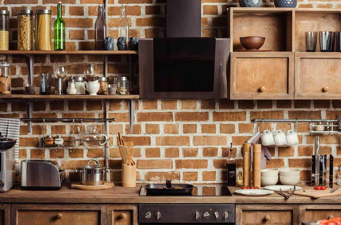Modern kitchen interior with wooden furniture and brick wall