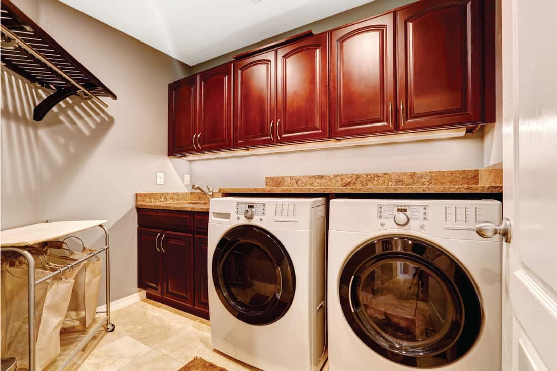 Modern laundry room interior with white appliances and cherry wood cabinets with granite tops
