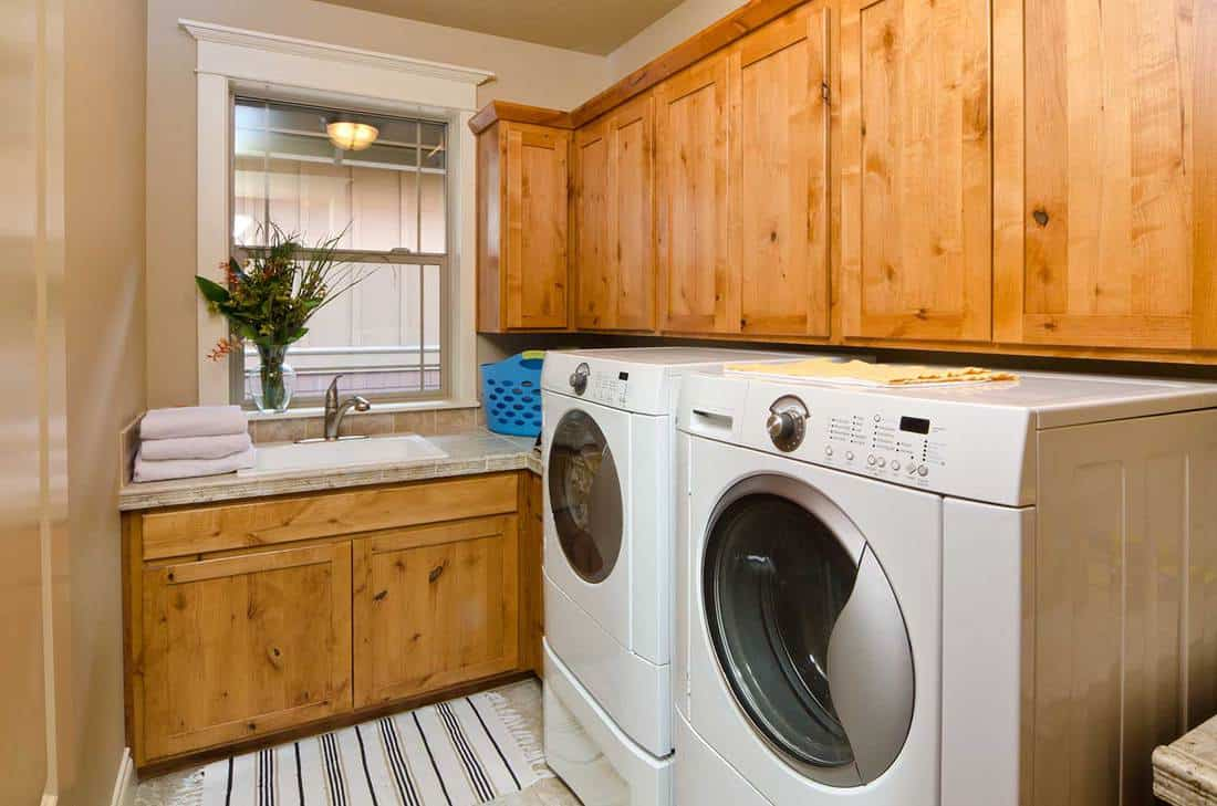 Modern laundry room with front loaders and wooden cabinets