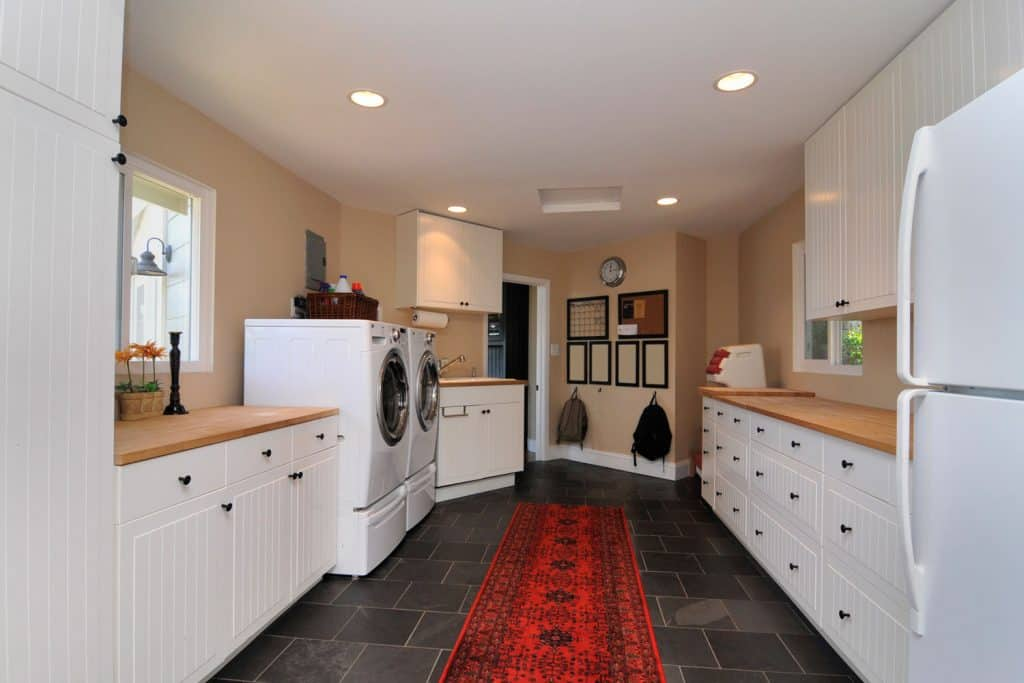 Modern laundry room with white paneled cabinetry, wooden countertop, and two washing machines on the side