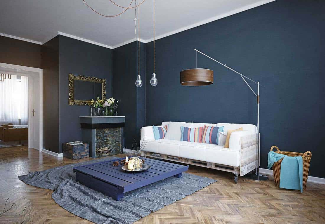 Modern living room interior with white sofa, blue wooden coffee table and carpet on parquet floor