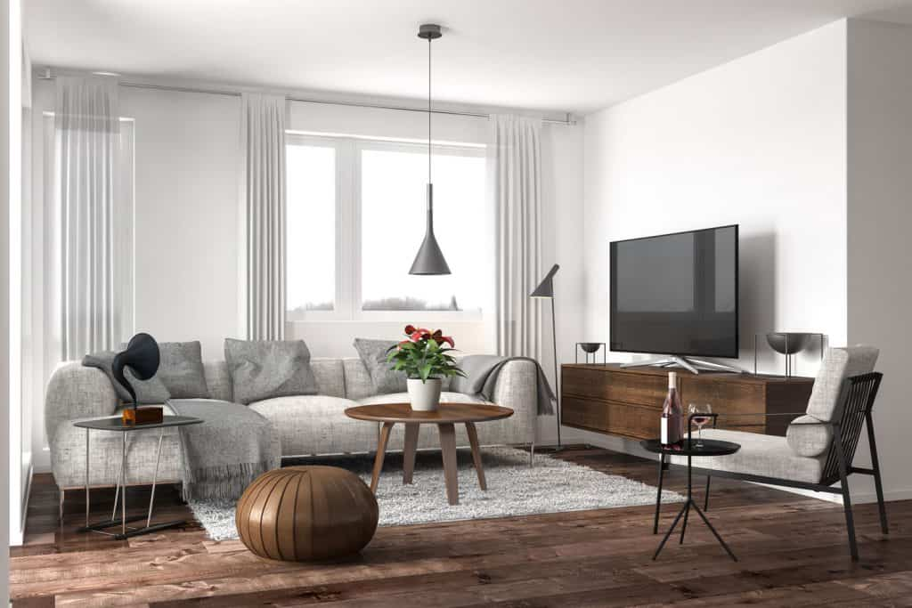 Modern luxurious contemporary living room with white painted walls, wooden flooring, and a light gray colored sectional sofa
