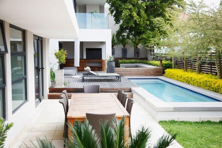 Modern patio next to swimming pool with outdoor furniture, What Kind Of Paint Can You Use On Outdoor Furniture?