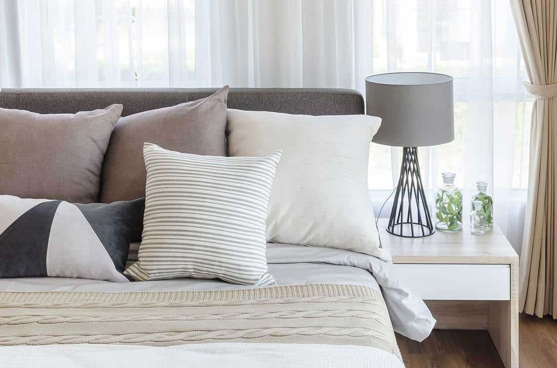 Modern style bedroom with pillows on bed and modern gray lamp on side table at home
