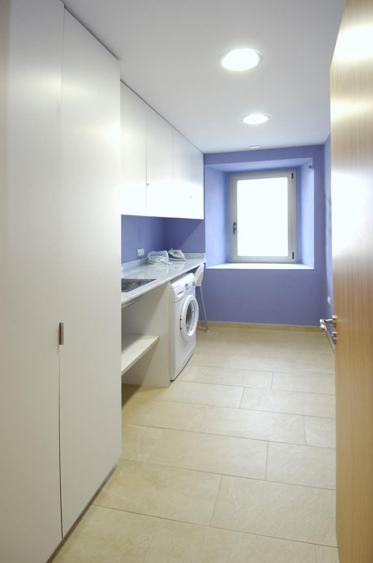 Neat laundry room with eye popping purple wall paint