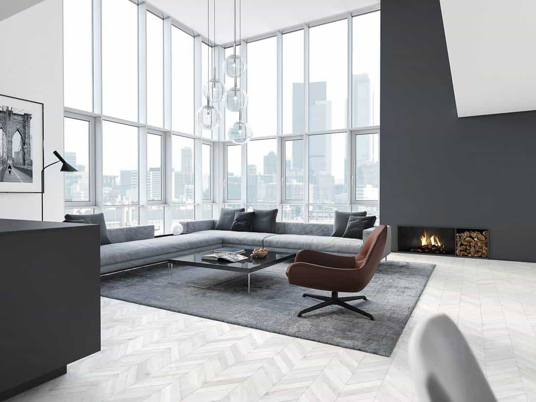 New modern scandinavian loft apartment with glass windows, gray corner sofa, fireplace and gray carpet on parquet floor