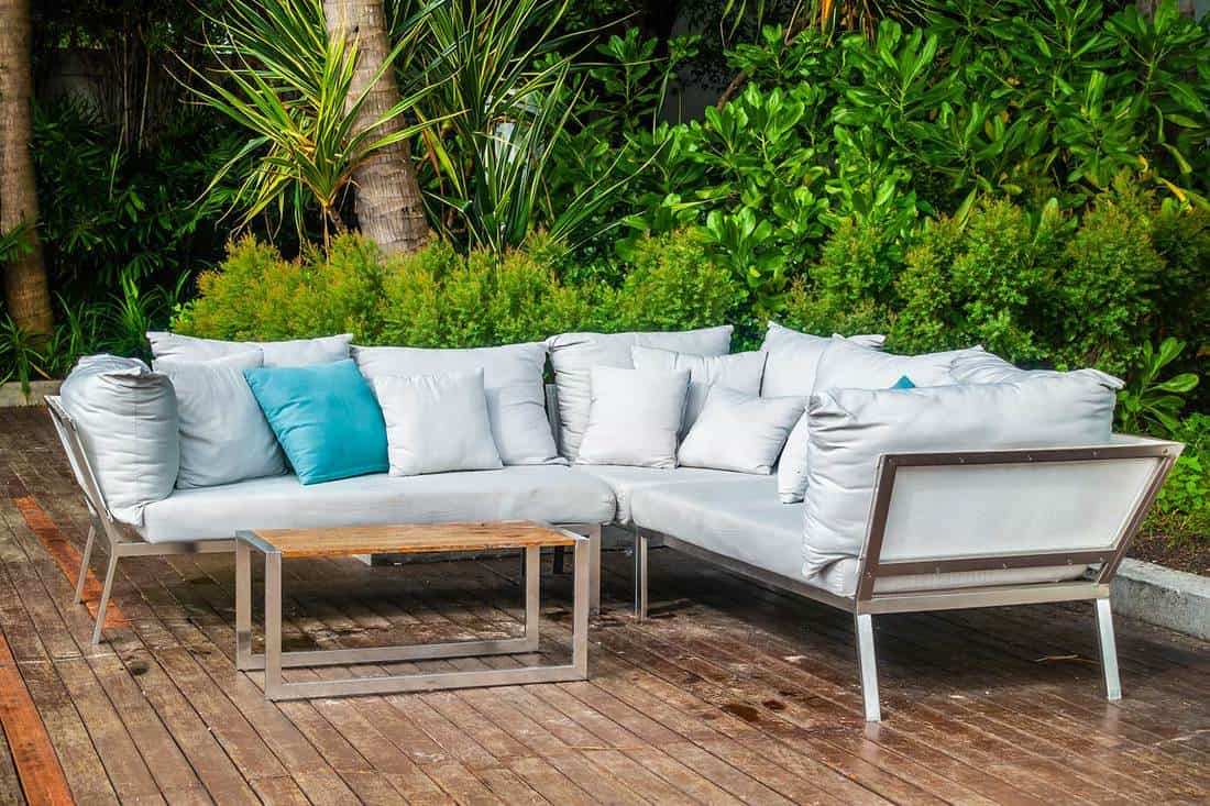 Outdoor wooden patio with pillow on sofa and nature view