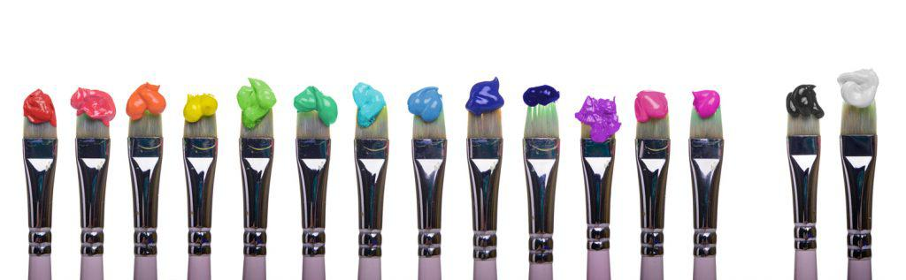 Paint Brushes dripping paint of various colors of palette