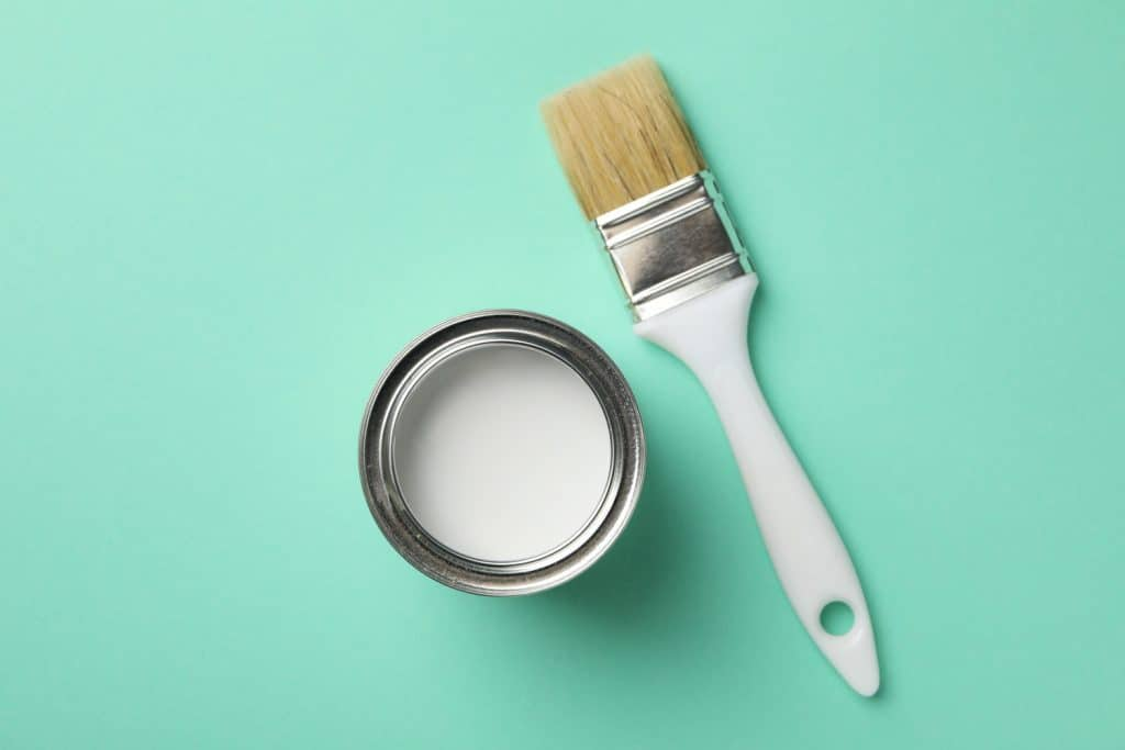 Paint can and brush on green background, top view