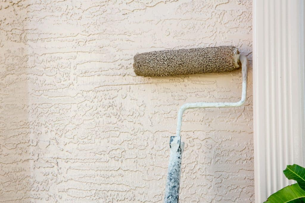 Paint roller is being used to paint the outside of a home. The roller is attached to a pole.