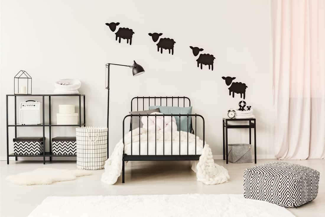 Patterned pouf near black bed with white bedsheets in teenager's bedroom with sheep stickers on the wall