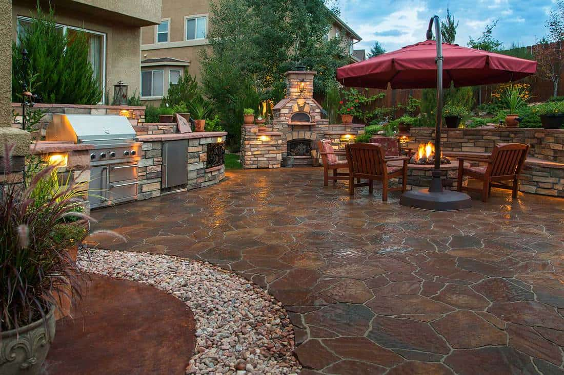 Paver patio with a fire pit, outdoor kitchen, pizza oven and lighting at dusk