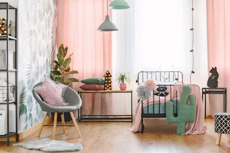 Pink pillow on grey armchair near bed in girl's bedroom interior with green cactus and lights on table, 21 Awesome Bedroom Chair Ideas To Check Out