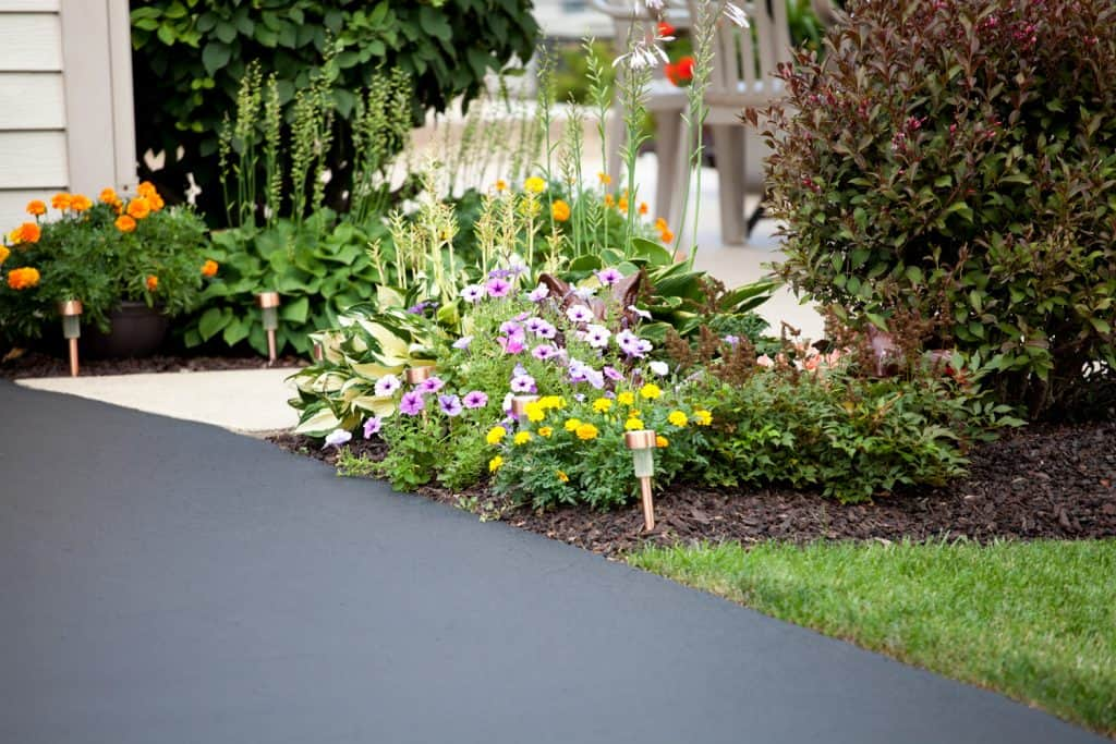 Pretty garden and entryway next to the paved driveway.