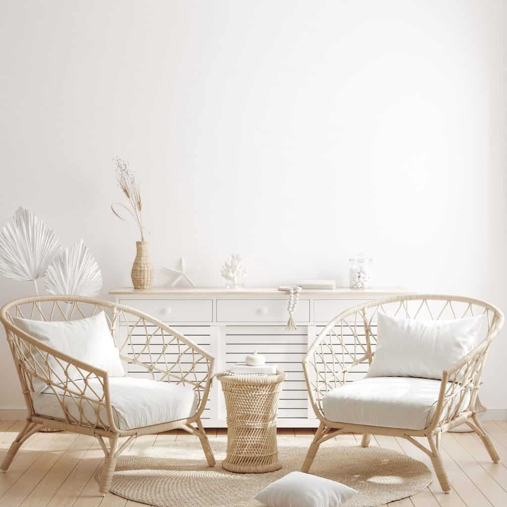 Rattan chairs and an end table on the middle inside a white themed living room