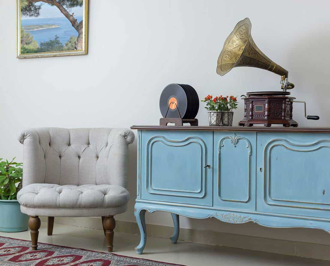 Retro off white armchair, vintage wooden light blue sideboard, old phonograph and vinyl records on background of beige wall, tiled porcelain floor, and red carpet