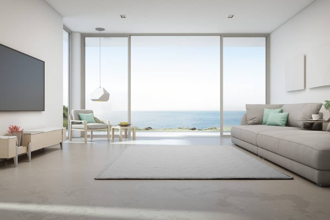 Sea view living room of luxury summer beach house with large glass door and wooden terrace. TV on white wall against big gray sofa in vacation home or holiday villa
