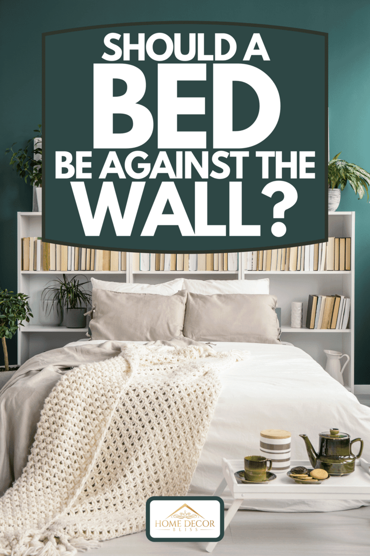 White bookshelf behind the double bed with blanket and pillows, plants and paintings in a green bedroom interior, Should A Bed Be Against The Wall?