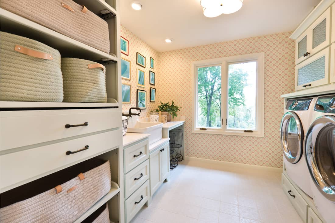 Showcase interior design of a utility laundry room in a residential home. with utility sink and fixture, washer and dryer, storage area.