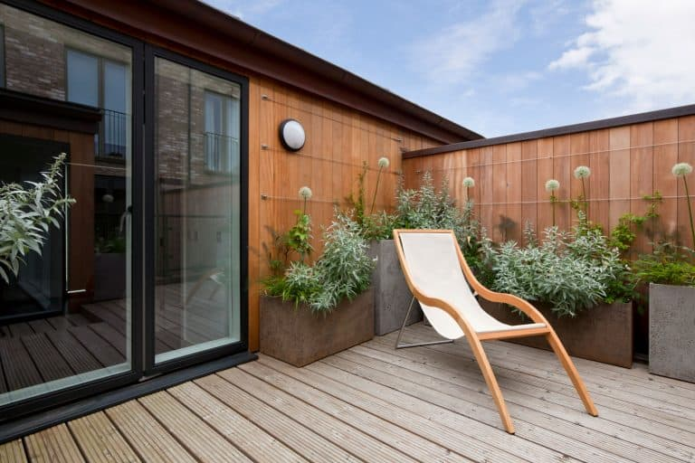 Simple attractive modern urban balcony garden with potted plants and reclining chair, What Are The Best Types Of Wood For Outdoor Furniture?