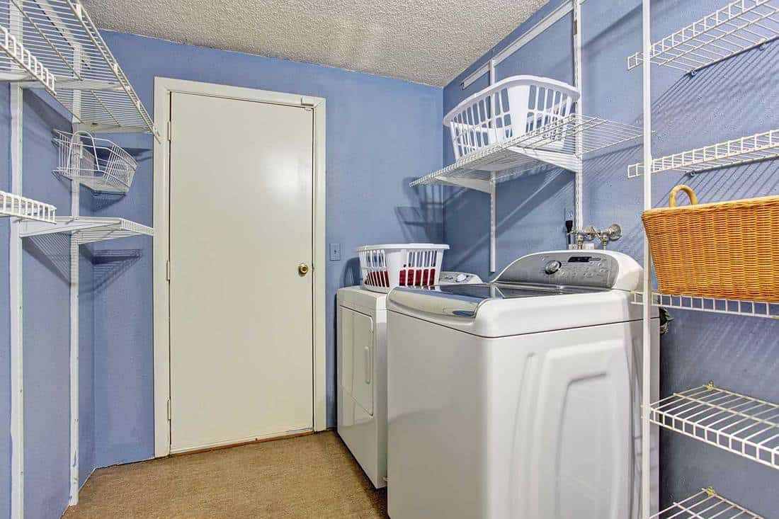 Small laundry room with periwinkle walls, washer and dryer