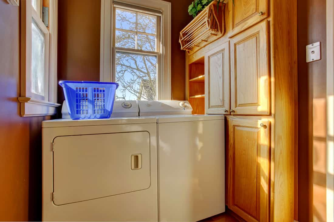 Small laundry room with wooden cabinet, white laundry appliances, and caramel brown wall paint