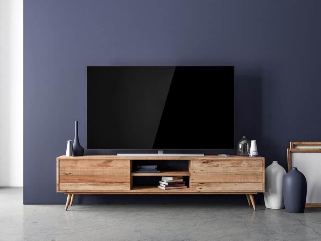 Smart TV standing on the wooden console in modern interior with home decor