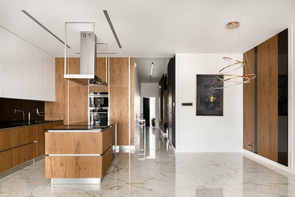Spacious kitchen in black and white with big kitchen island, wooden elements and marble floor